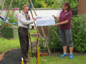 Cllr Phil Matthews, Mayor of Wilton, officially opens the community garden and presents a cheque for £1,300 to Charlotte Blackman, Chair of the Trustees.